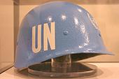 """Exposition d'un casque bleu frappé des lettres """"UN"""" pour United nations."""
