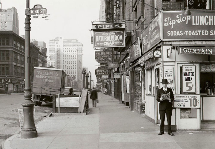 A man reads a newspaper on New York's 6th Ave. and 40th S on May 18, 1940